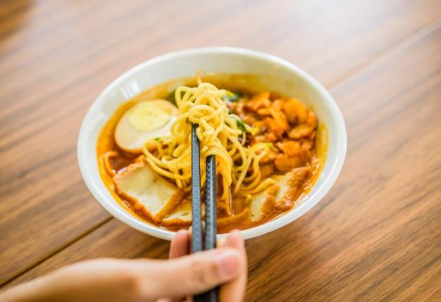Hand mit den chinesischen essstäbchen, die malaysia-garnelennudeln-currysuppe essen.