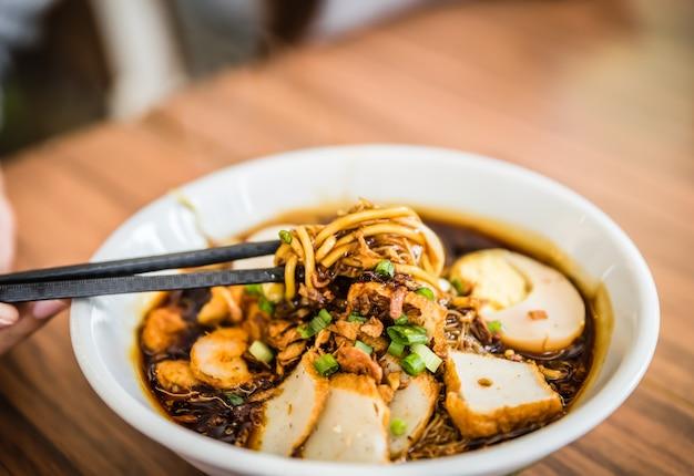 Hand mit den chinesischen essstäbchen, die malaysia loh mee suppe essen.