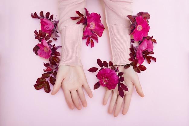 Hand mit den rosa blumen und blumenblättern, die auf einer papierwand, kosmetik für handhautpflege liegen. natürliche blütenkosmetik, ätherische öle, anti-falten- und anti-aging-handpflege