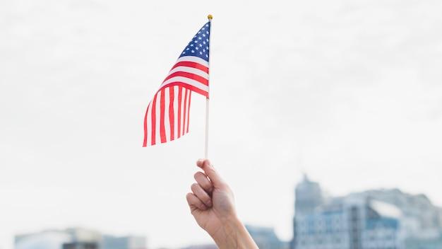 Hand mit der amerikanischen flagge in der luft winken