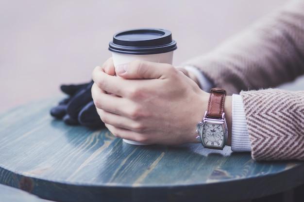 Hand mit der uhr, die kaffee im straßencafé hält
