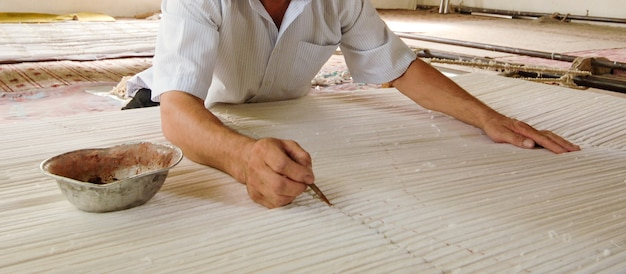 Hand mit einem bleistift macht markierungen auf der teppichweberei und herstellung von handgefertigten teppichen nahaufnahme