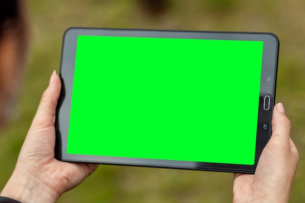 Hand mit einem darauf liegenden tablett, nahaufnahme der kartentasche, green-screen-modell, layout.