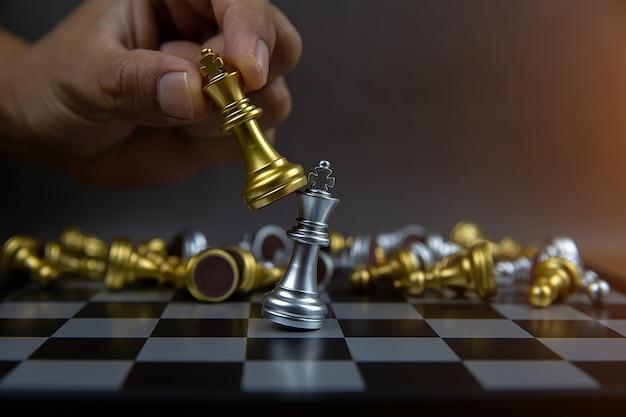 Hand mit einem goldenen königsschach tötet ein silbernes königsschach.
