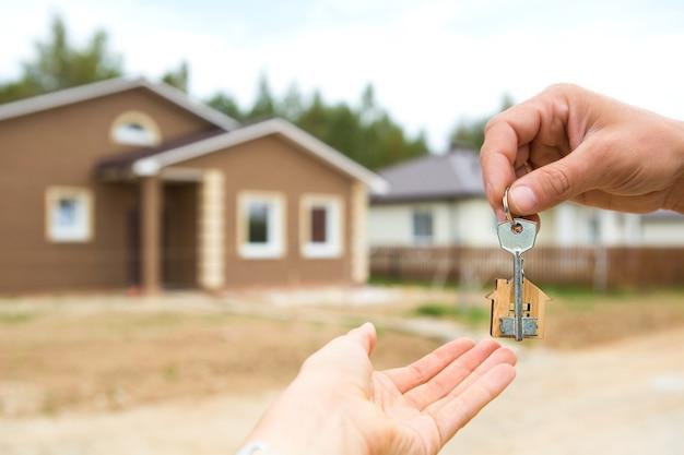 Hand mit einem schlüssel und einem hölzernen schlüsselringhaus. bauen, projektieren, in ein neues zuhause umziehen, hypothek aufnehmen, immobilien mieten und kaufen. zum öffnen der tür. speicherplatz kopieren