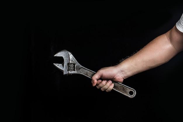 Hand mit einem schraubenschlüssel