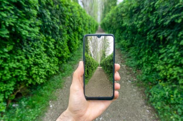 Hand mit einem smartphone-bild auf dem hintergrund von naturgrün und der straße im parkfotografie-internet und vernetzung im reisekonzept hochwertiges foto