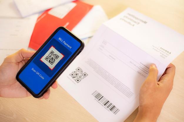 Hand mit einem smartphone zum scannen eines qr-codes