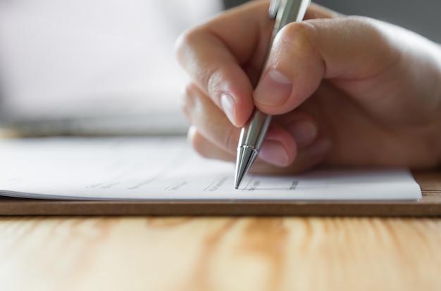 Hand mit einem stift auf einem papier