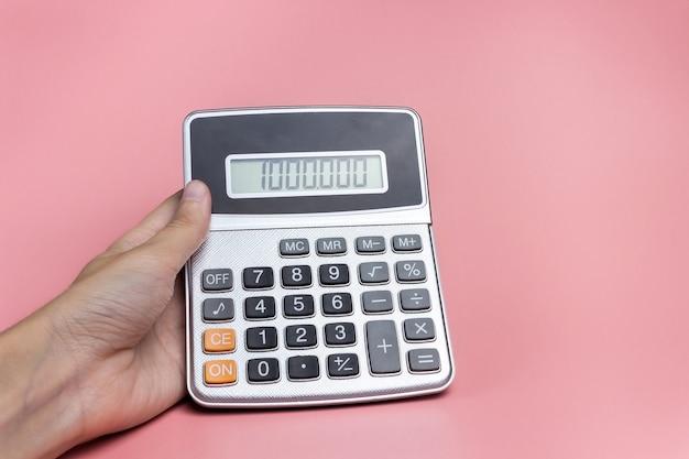 Hand mit einem taschenrechner auf rosa hintergrund. das konzept von finanzen, geschäft, geld, buchhaltung, sparen