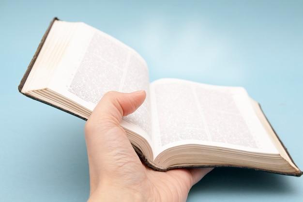 Hand mit einer offenen bibel mit lichtstrahlen auf einem blauen hintergrund