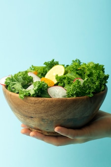 Hand mit einer schüssel salat auf blau