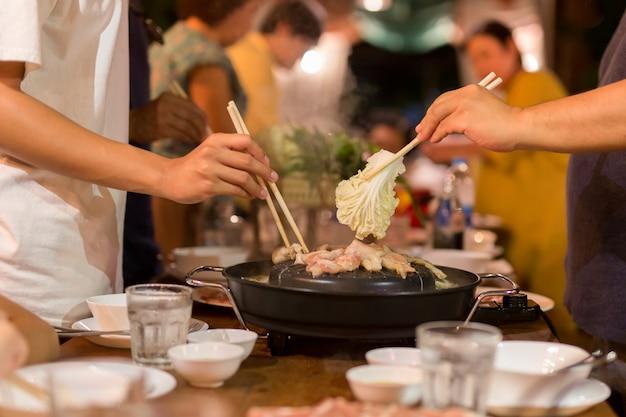 Hand mit essstäbchen, der grillschweinefleisch und gemüse beim familienessen kocht.
