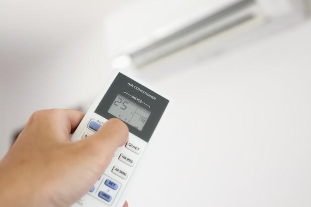 Hand mit fernbedienung auf klimaanlage im raum gerichtet