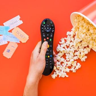 Hand mit fernbedienung über popcorn und kinokarten