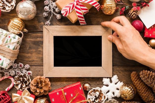 Hand mit fotorahmen zwischen weihnachtsdekorationen