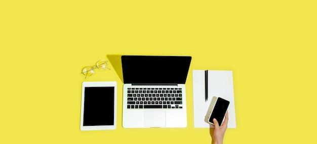 Hand mit gadgets, geräten in der draufsicht, leerer bildschirm mit kopienraum, minimalistischer stil. technologien, modern, marketing. negativer platz für anzeige, flyer. gelbe farbe im hintergrund. stilvoll, trendig.