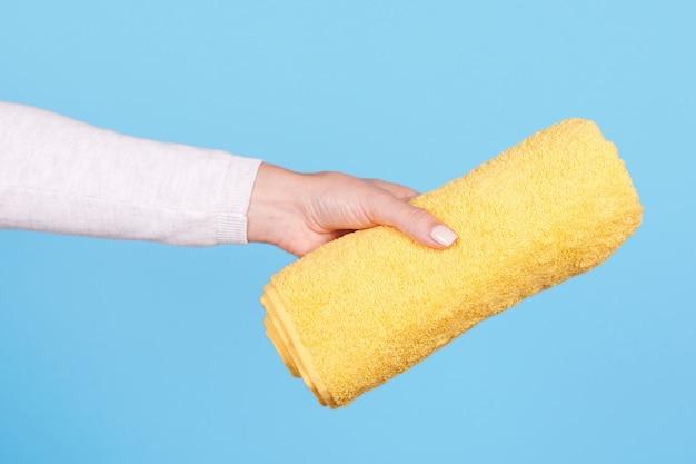 Hand mit gefaltetem gelbem handtuch isoliert