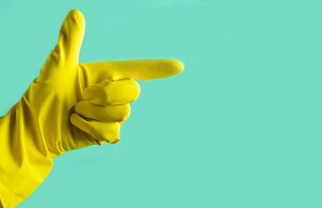 Hand mit gelbem gummihandschuh zeigt in die seite, reinigungskonzept, kopierraum