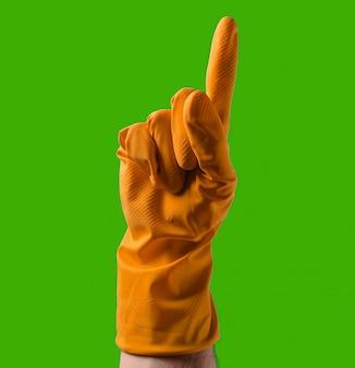 Hand mit gelben gummihandschuhen zeigt mit dem zeigefinger nach oben