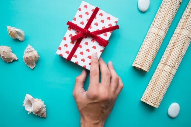 Hand mit geschenkbox und dekorativen elementen
