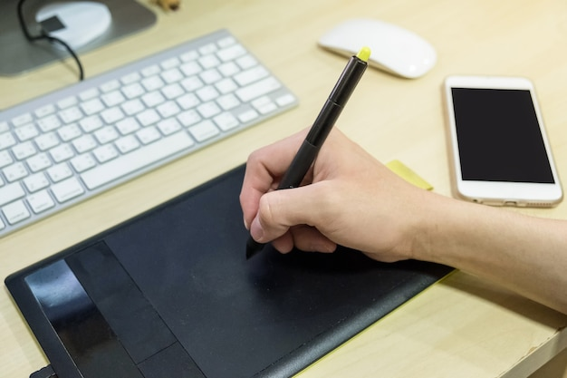 Hand mit grafiktablett mit smartphone auf dem schreibtisch am arbeitsplatz