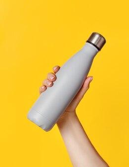 Hand mit grauer wiederverwendbarer isolierter flasche auf gelbem hintergrund. null abfall, plastikfreies und nachhaltiges lifestyle-konzept