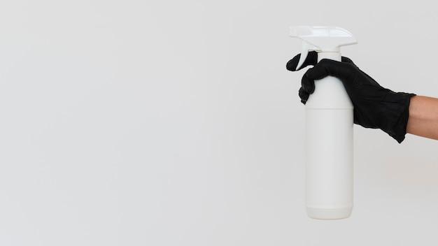 Hand mit handschuh, der desinfektionsmittel in flasche mit kopierraum hält