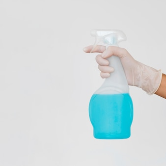 Hand mit handschuh, der die reinigungslösungsflasche hält