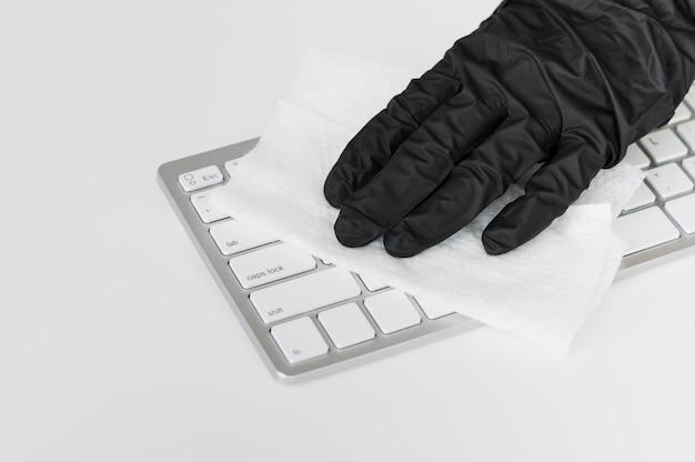 Hand mit handschuh, der die tastaturoberfläche desinfiziert Premium Fotos
