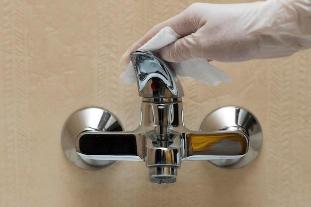 Hand mit handschuh desinfizieren wasserhahn