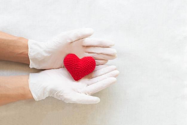 Hand mit handschuhen, die rotes herz halten. medizinische herzgesundheit, kardiologie, versicherung, organspende.