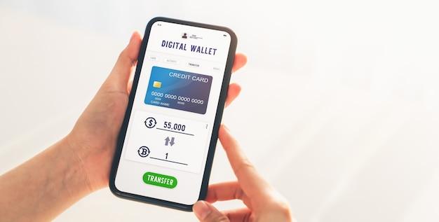 Hand mit handy für bitcoin-dollar-umtausch-anwendung. smartphone-bildschirm zeigt zahlung mit kreditkarte an.