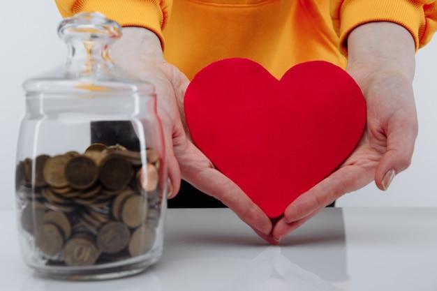 Hand mit herz und münzen im glas.