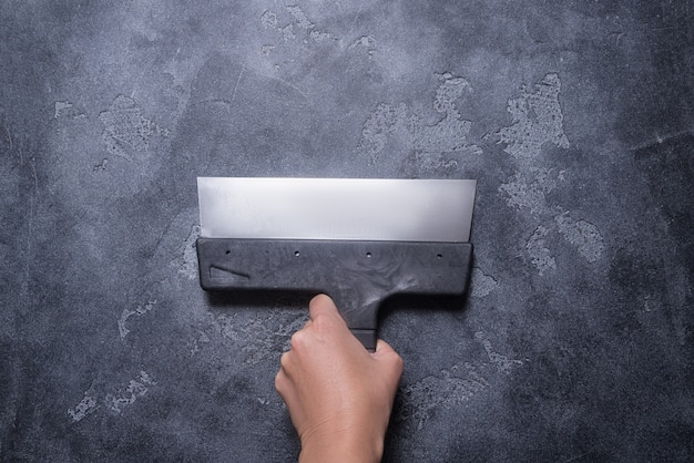 Hand mit kittmessern auf grauem hintergrund
