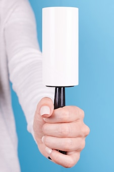 Hand mit klebriger walze zur stoffreinigung isoliert