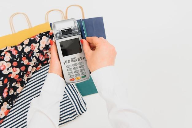 Hand mit kreditkarte durch terminal zum verkauf im supermarkt wischen