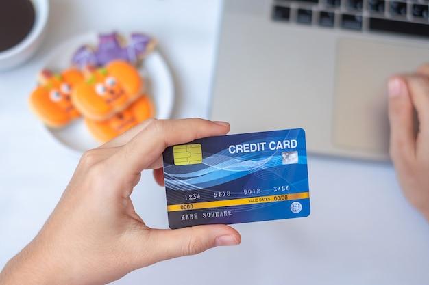 Hand mit kreditkarte für online-shopping auf dem laptop während des essens von halloween-keksen und kaffee. fröhliches halloween, hallo oktober, herbstherbst, fest-, party- und urlaubskonzept