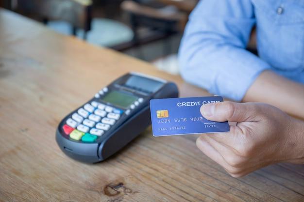 Hand mit kreditkarte, mann, der kreditkarte mit einem kreditkartenlesegerät am bartheke hält, kunde, der mit kontaktloser kreditkarte mit nfc-technologie zahlt