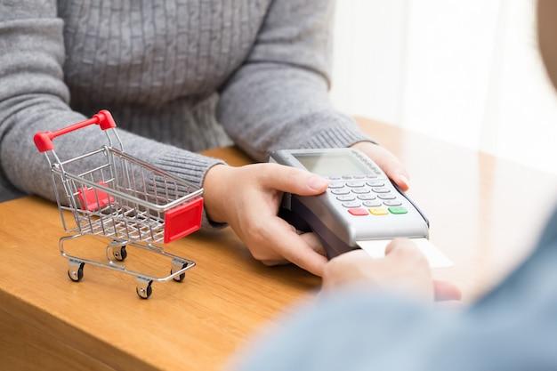 Hand mit kreditkarte swipe durch terminal für die zahlung