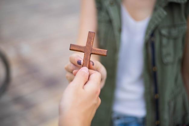 Hand mit kreuz. konzept der hoffnung, des glaubens, des christentums, der religion, der kirche online.