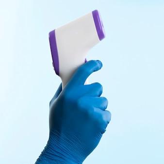 Hand mit latexhandschuh, der das thermometer hält