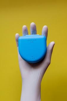 Hand mit latexhandschuh, der eine plastikbox hält, um schienen zu transportieren