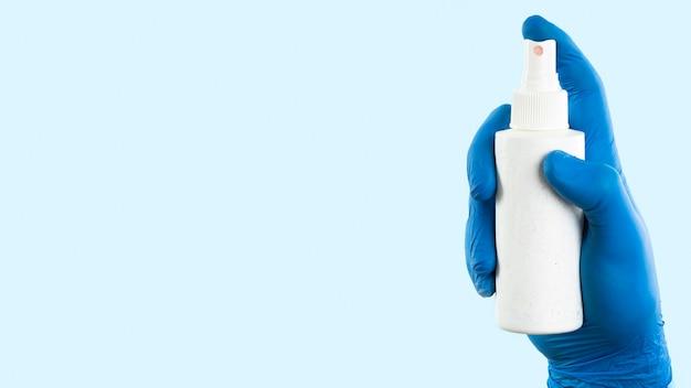 Hand mit latexhandschuh, der sprühflasche mit kopierraum hält