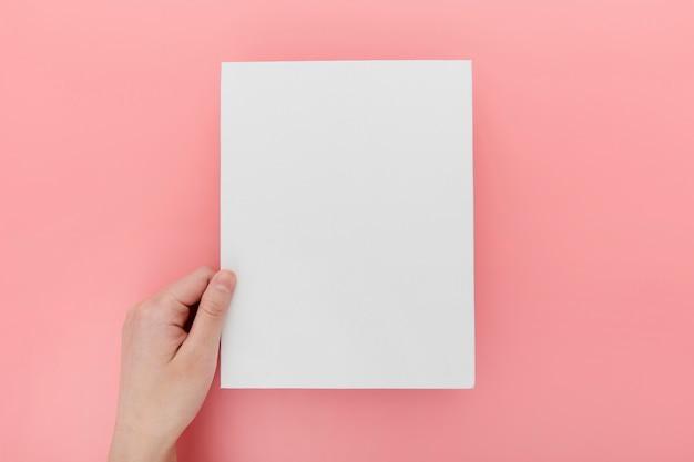 Hand mit leerer broschüre auf dem schreibtisch