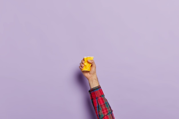 Hand mit leerer zerknitterter tasse kaffee über lila