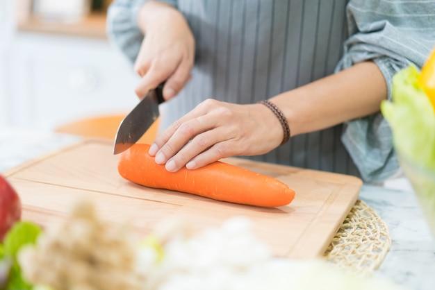Hand mit messer schneiden karotte. frau bereitet essen am tisch zu.