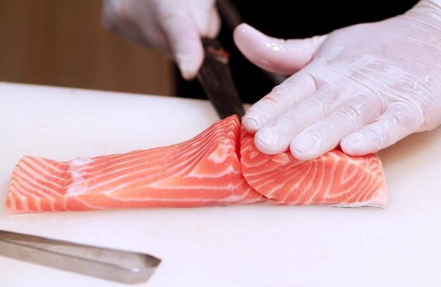 Hand mit messer schneidet lachsfische. rohfische auf dem kochen des brettes. chef bereitet rohen fisch für jap vor