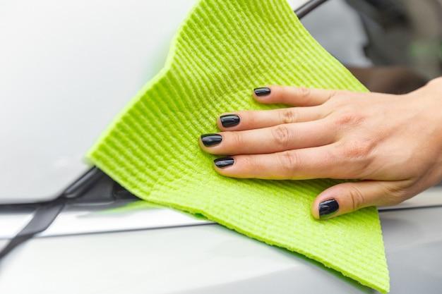 Hand mit mikrofasertuch-reinigungsauto