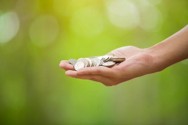 Hand mit münzen auf bokeh hintergrund. geldkonzept